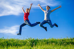 Two kids jumping on green hills against blue sky. Two happy kids jumping on green hills against blue sky with clouds Stock Photos