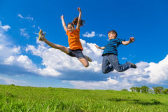 Two kids jumping on green hills. Two happy kids jumping on green hills against blue sky Royalty Free Stock Image