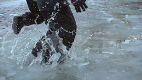 Two kids jumping in spring icy puddle, slow motion 250 fps stock footage