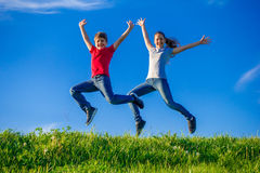 Two kids jumping together on green spring hills. Two happy kids jumping together on green spring hills against blue sky Royalty Free Stock Images