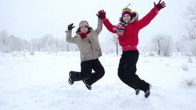 Two kids jumping together on winter landscape, slow motion. Two active kids jumping together on winter snow landscape, slow motion 250 fps stock video
