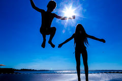 Two kids jumping on trampoline. Silhouette of two kids jumping on trampoline against blue sky stock photography