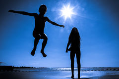 Two kids jumping on trampoline. Silhouette of two kids jumping on trampoline against blue sky royalty free stock images