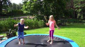 Two kids jumping on trampoline stock footage