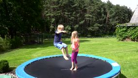 Two kids jumping on trampoline stock video