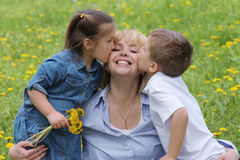 Two kids kissing mother on cheek. Two kids kissing mother among dandelion field Royalty Free Stock Photo