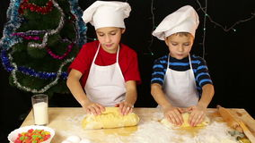 Two kids kneading the dough for christmas cookies stock video footage
