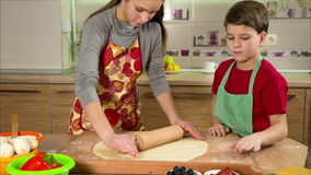 Two kids kneading the dough, making the pizza stock video footage