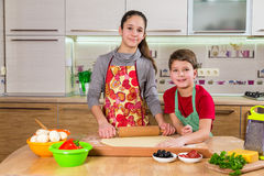 Two kids kneading the dough for making the pizza Stock Image
