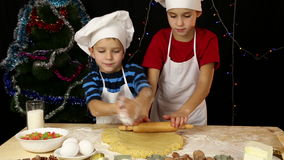 Two kids kneading the dough for xmas cookies together stock footage