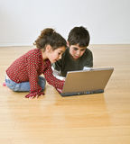 Two kids with laptop computer. On the floor Royalty Free Stock Photography