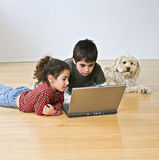 Two kids with laptop computer and a dog. Two kids and a dog with laptop computer on the floor stock image