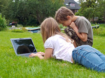 Two kids with laptop, in the grass Royalty Free Stock Photography