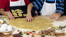 Two kids lay out the dough for xmas cookies to baking tray stock video footage