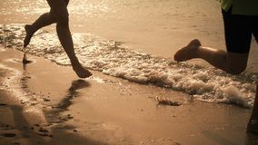 Two kids legs running at the beach, slow motion stock footage