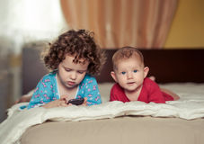 Two kids lie on a bed Royalty Free Stock Image