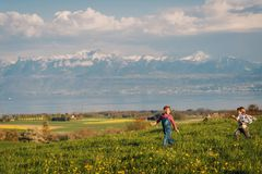 Two kids, little brother and big sister, playing together outdoors in swiss fields with view on lake Geneva. And french mountains Haute-Savoie. Image taken in Royalty Free Stock Photos