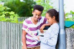 Two kids looking at map. Smiling two kids looking at map standing near the pole royalty free stock image