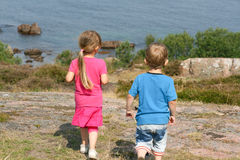 Two Kids Looking at Water. A girl and a boy on top of large large looking at the ocean Royalty Free Stock Photo