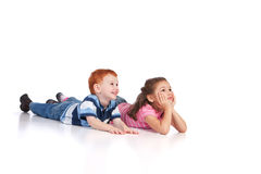 Two kids lying on floor. And watching something. Isolated background, reflection foreground Royalty Free Stock Photos