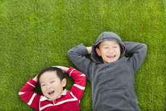 Two kids lying on the meadow in the park Stock Photos