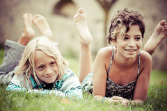 Two kids lying on top of grass Stock Images