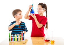 Two kids making chemical experiment. Two smiling kids making chemical experiment, isolated on white Royalty Free Stock Image