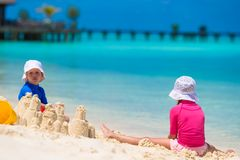 Two kids making sand castle and playing at Stock Photography