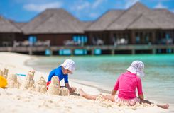 Two kids making sand castle and playing at Royalty Free Stock Images