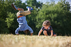 Two kids making a somersault. And smiling in the nature Royalty Free Stock Photo