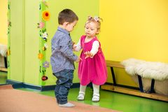 Two kids in Montessori preschool Class. girl and boy playing in kindergarten. Two kids in Montessori preschool Class. Little girl and boy playing in kindergarten royalty free stock image