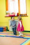Two kids in Montessori preschool Class. Little girl and boy playing in kindergarten Stock Image