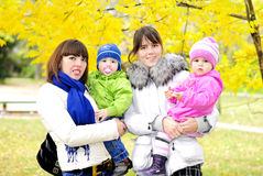 Two kids with mums on a green glade. In the autumn Royalty Free Stock Photos