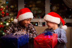 Two kids near Christmas presents. Stock Photo