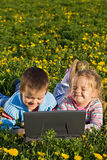 Two kids outdoors having fun with a laptop Stock Photos