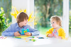 Two kids painting and cutting colorful paper butterflies. Two kids, happy teenager boy and his cute toddler sister, having fun together drawing, painting and royalty free stock images
