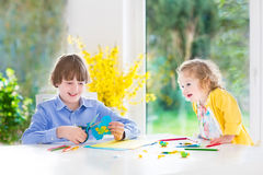 Two kids painting and cutting colorful paper butterflies Stock Photography