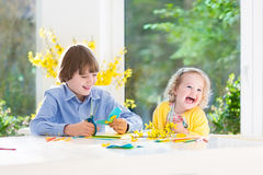 Two kids painting and cutting colorful paper butterflies Stock Image