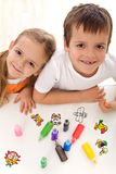 Two kids painting with lots of colors Royalty Free Stock Photo