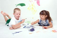 Two kids are painting pictures. A couple of young kids are painting pictures on a large white sheet of background paper Royalty Free Stock Images