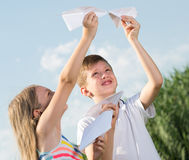 Two kids with paper planes outdoors. Two happy smiling kids playing with flying paper planes outdoors Royalty Free Stock Images