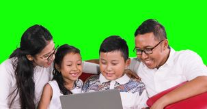 Two kids and parents use laptop on sofa stock footage