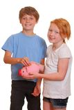 Two kids with piggy bank Stock Photos