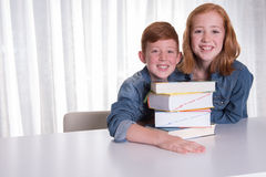 Two kids and a pile of books Stock Image