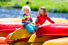 Two kids on piles of kayak. Family on kayak tour. Two kids sitting on pile of kayaks at a river shore on a sunny day. Children in summer sport camp. Active stock images