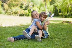 Two kids with pinwheels playing at park Stock Photos