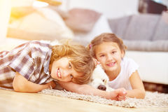 Two kids play at home with dog Stock Image