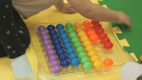 Two kids play an intelligent game with small balls. Two kids play an intelligent game with colorful small balls. Closeup stock video footage