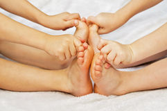 Two kids play with their toes. Two kids feet touching, with hands grabbing toes Royalty Free Stock Photography