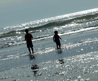Two Kids Playing on the Beach as the Sun is Glistening on the Wa Royalty Free Stock Image